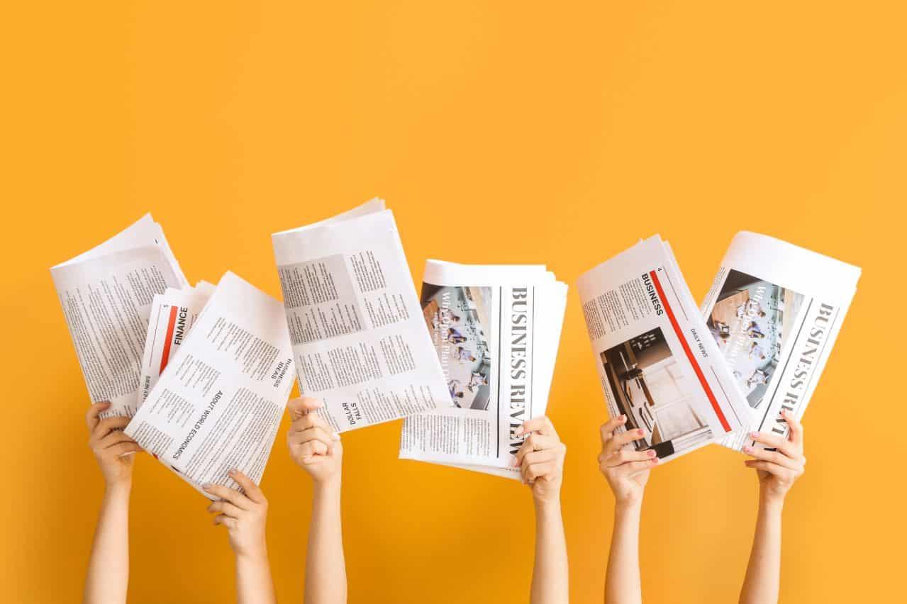 Un groupe de personnes portant des journaux