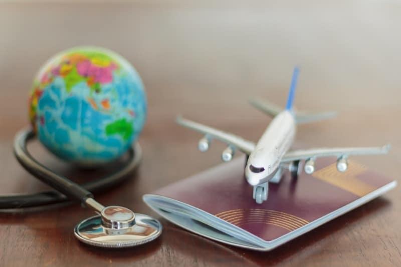 Photo qui montre un petit avion en plastique au-dessus d'un passeport à coté d'un petit globe terreste en plastique et un stratoscope