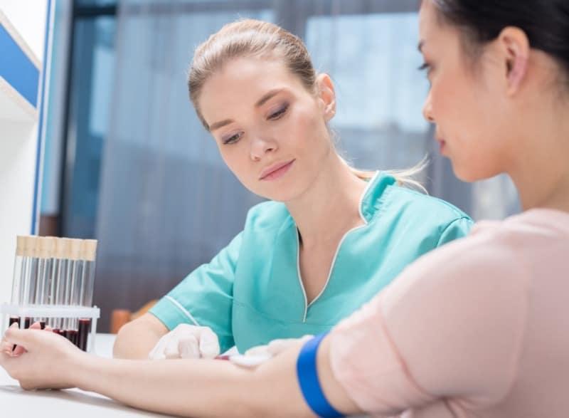 Infirmière réalisant une prise de sang sur une patiente